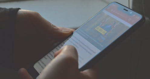 Hands scrolling a news article on a phone