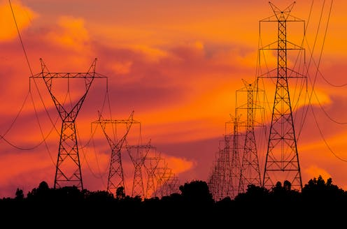 Electricity towers against a sunset.