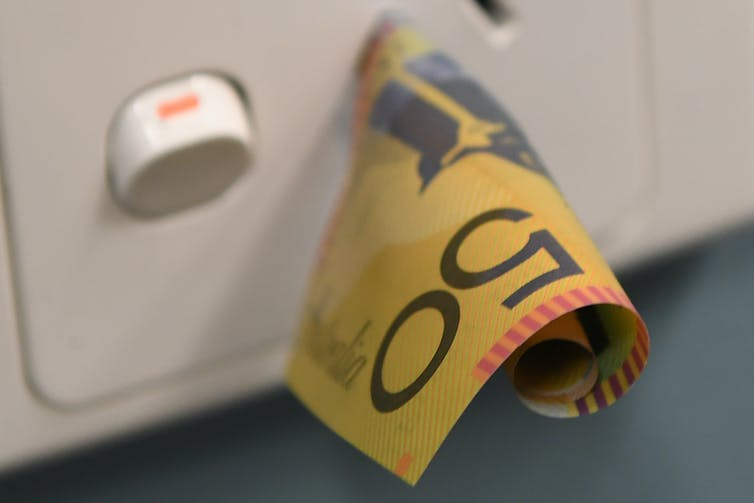 A $50 note sticking out of a power socket.