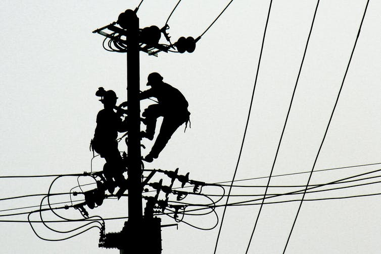 Workers perform maintenance on power lines.