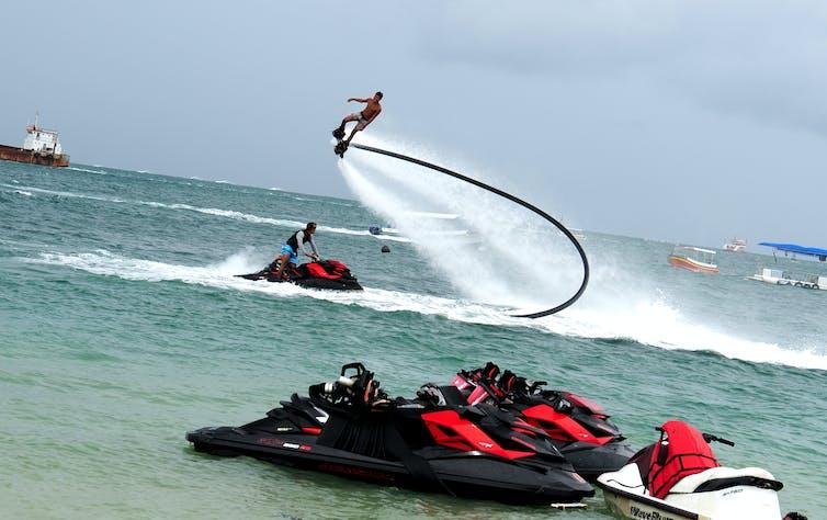 Seorang pemandu wisata memperagakan atraksi gerakan salto dengan 'flyboard' di kawasan pantai wisata bahari Tanjung Benoa, Bali.