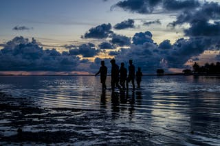 A group of people cross a shallow lagoon at dusk in the tropics.