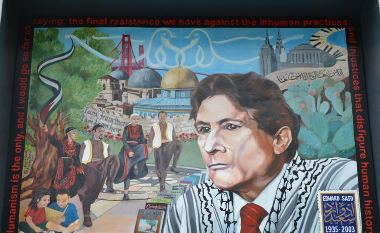Mural of Edward Said surrounded by people dancing and his books.