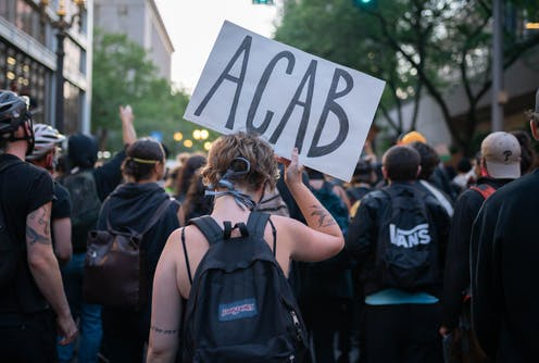 Female protester holds sign with letters 'ACAB'