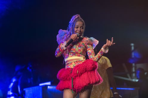 A female singer colourfully dressed in a red African skirt holds a microphone to her mouth as she performs on stage.