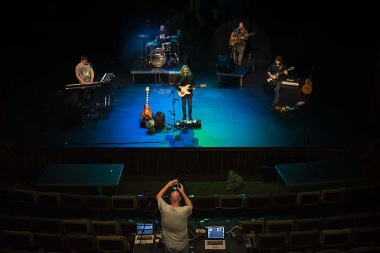 A sound engineer in an empty auditorium records a band of live musicians on a stage that is bathed in blue light.