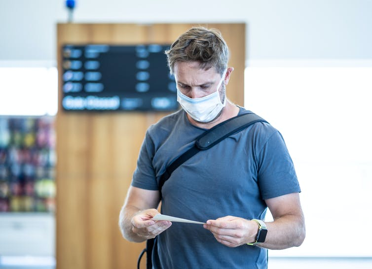 Man in mask at airport, looking at ticket.