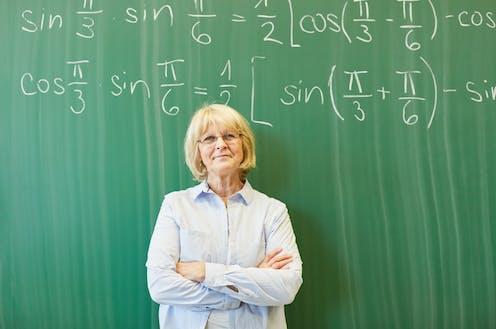 Profesora veterana ante una pizarra con fórmulas matemáticas