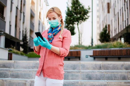 Woman wearing face mask and gloves looking at phone