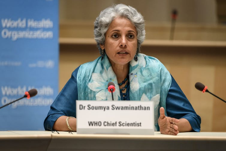 World Health Organization chief scientist Soumya Swaminathan sits in front of microphones