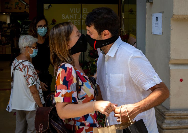 A couple wearing face masks kiss in Barcelona.