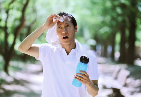 A man wearing a t-shirt holding a water bottle and wiping sweat off of his brow.