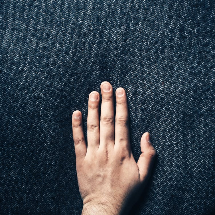 A hand touching a dark blue fabric.