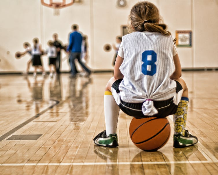A young girl sits on a basketball while wearing a sports jersey.