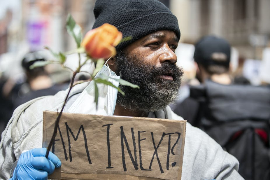 """A Black man at a demonstration holding a sign, """"Am I next?"""""""