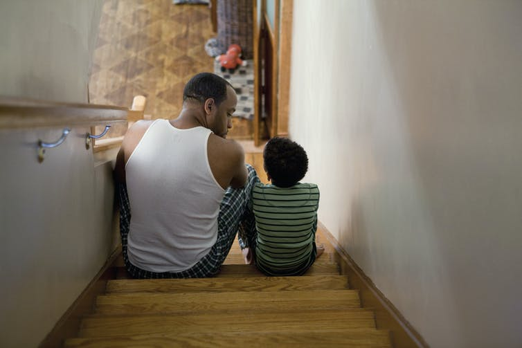 A man and a boy sitting on the stairs.