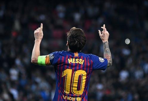 Lionel Messi de espaldas, con camiseta del Barça, señalando al cielo con los índices de las manos.
