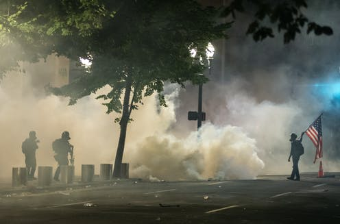 Protester carrying an American flag and two heavily armed federal agents are seen in silouhete against a backdrop of tear gas