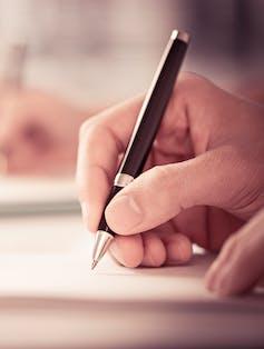 A hand holding a pen.