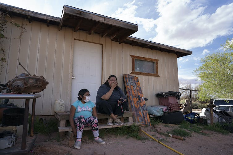 A mother and daughter sit outside their home on the Navajo Nation reservation.
