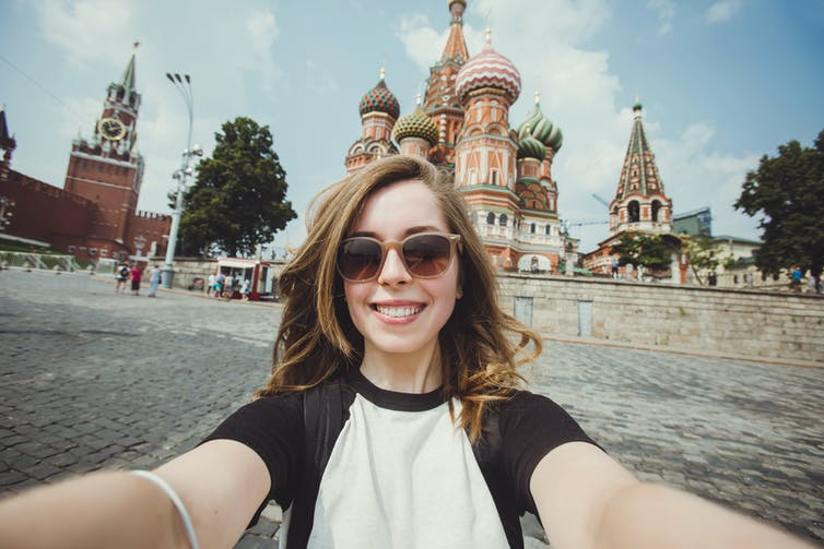 Young woman taking a selfie against Russian skyline.
