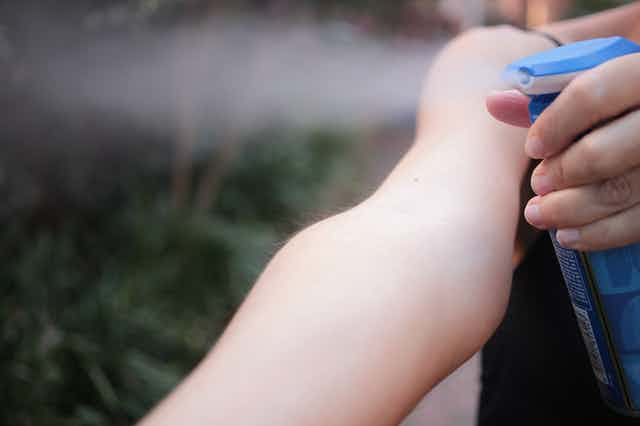 Person sprays repellent onto their outstretched arm.