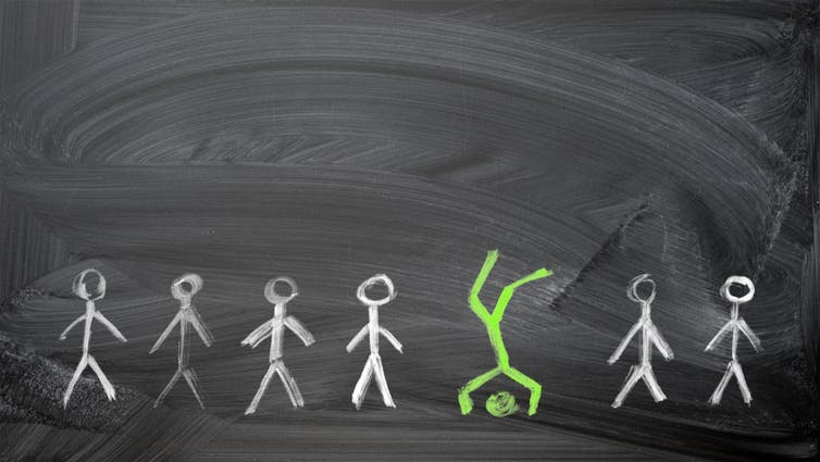 Stick men drawn in white chalk on a blackboard with the odd one out in green chalk balancing on his head