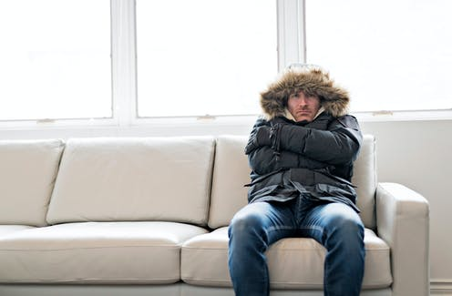 Man in thick jacket sitting on couch in cold house