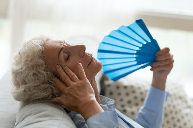 Elderly women fanning herself as she struggles with the heat in her house