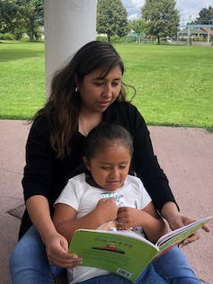 A mother reading to her daughter.