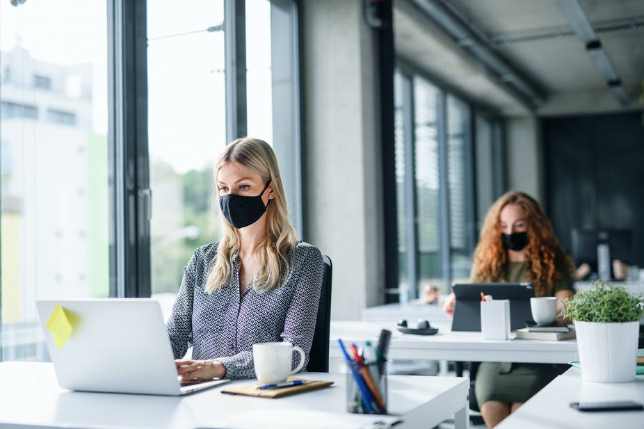 Office workers wearing face masks and sat apart.