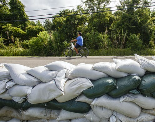 A child cycles past a wall of sand bags.
