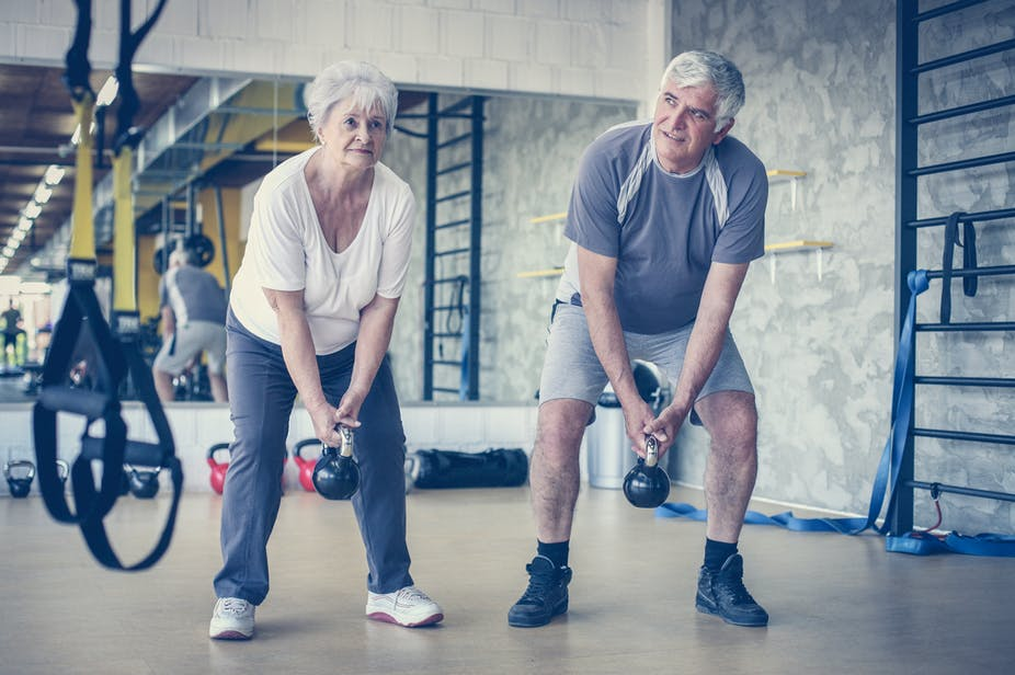 Older couple lifting kettlebells at the gym.