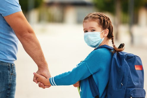a young girl with braided hair wearing a blue cardigan and surgical mask holds her father's hand
