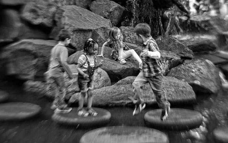 Black-and-white photo of children splashing in rocks.