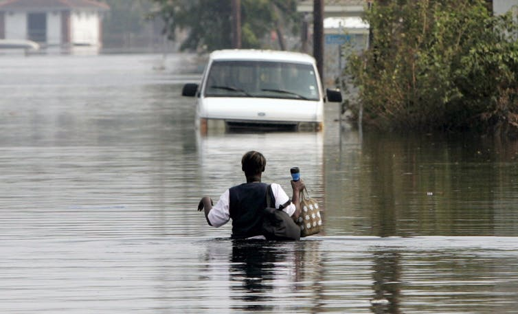 A person wades through chest-high flood water towards an abandoned car.