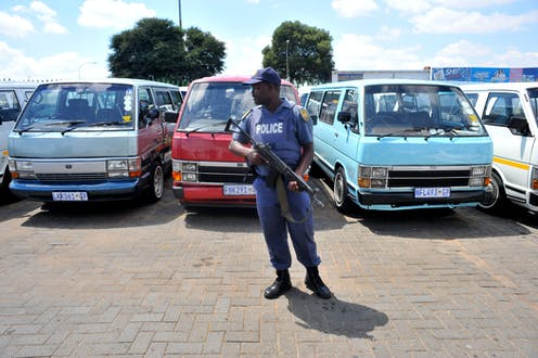A policeman with a rifle in a parking lot guards empty minibus vehicles that form a row behind him