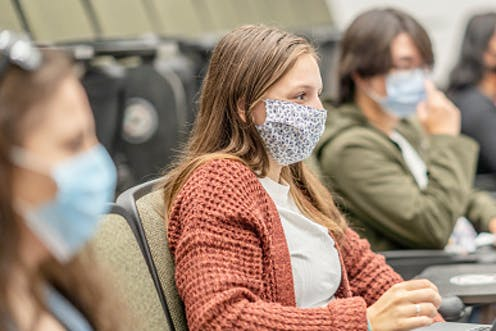 A female college student wearing a mask sits in a class next to other students with her laptop open.