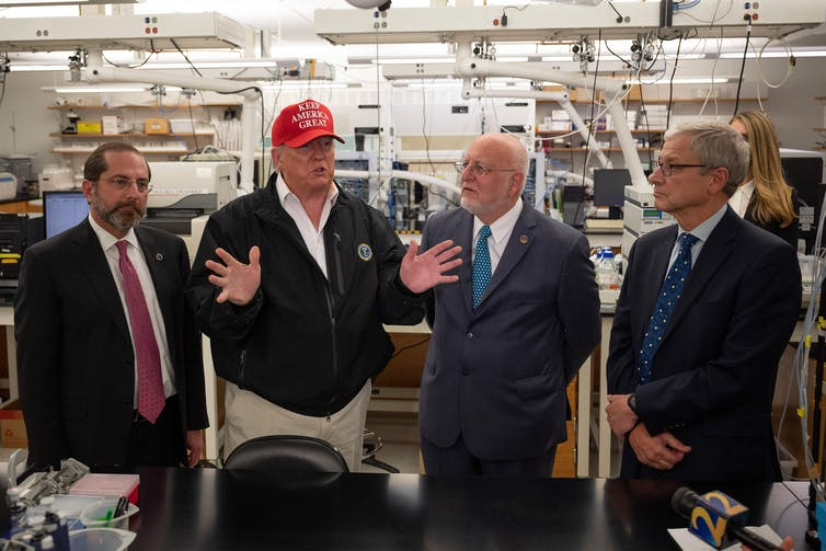 Trump, wearing khaki pants and a MAGA hat, surrounded by health officials at the CDC.