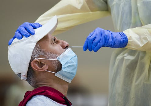 A man in profile wearing a white baseball cap and a face mask pulled down below his nose, winging as the gloved hand of a health-care worker inserts a test swab into his nose.