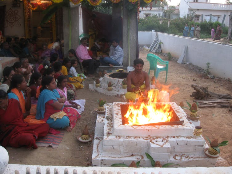 A man sits at a fire altar