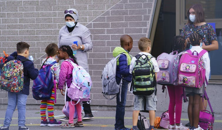 Teachers wearing face masks greet students in a school yard.