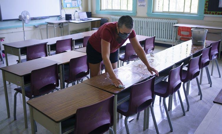 A teacher washes desks.