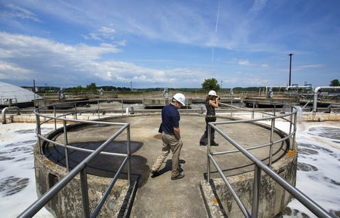 two people overlook an aeration system at a wastewater treatment plant