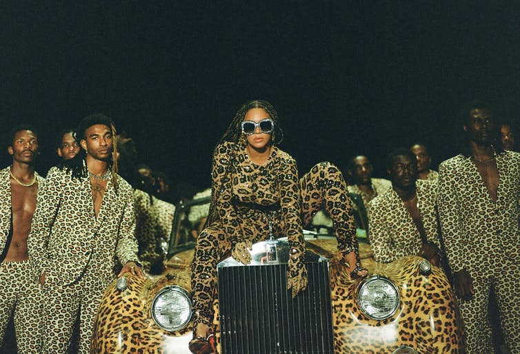 Singer Beyonce in leopard print on car with suited men