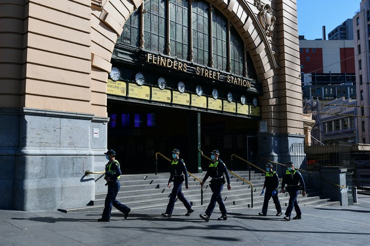 Police officers walking past an empty Flinders Street Station