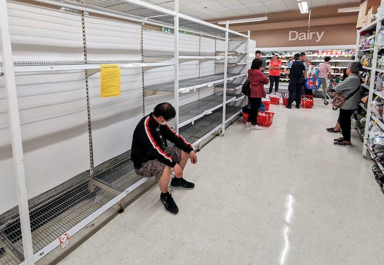 A man sits on an empty supermarket shelf.