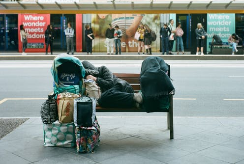 Homeless person resting on bench with belongings piled in front
