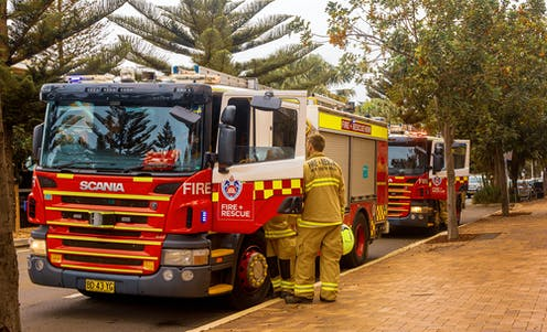 Firefighters getting into a fire truck beside a footpath.