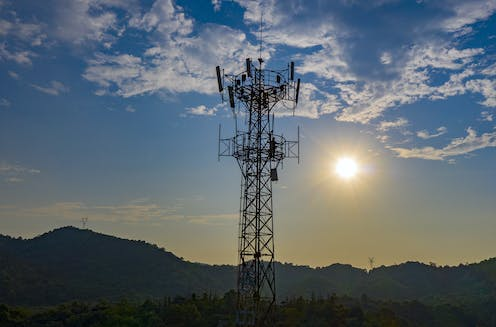 A 5G mobile tower silhouetted against hills and a low sun.